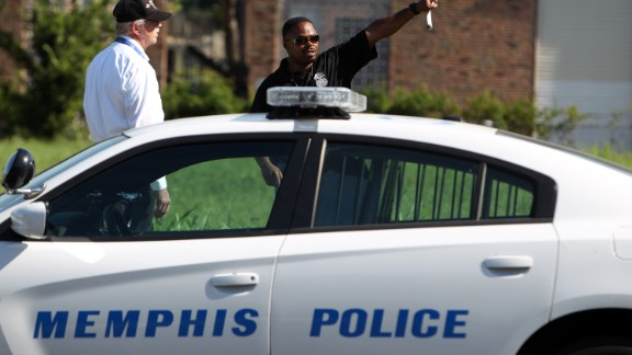 Memphis police canvas an area near where Police Officer Sean Bolton was fatally shot during a traffic stop Saturday, in Memphis, Tenn., Sunday, Aug. 2, 2015. (Mike Brown/The Commercial Appeal via AP)