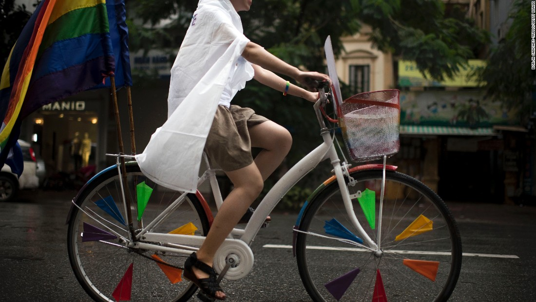 A Vietnamese woman rides a bicycle decorated with rainbow flags at the bike rally on August 2 in Hanoi.