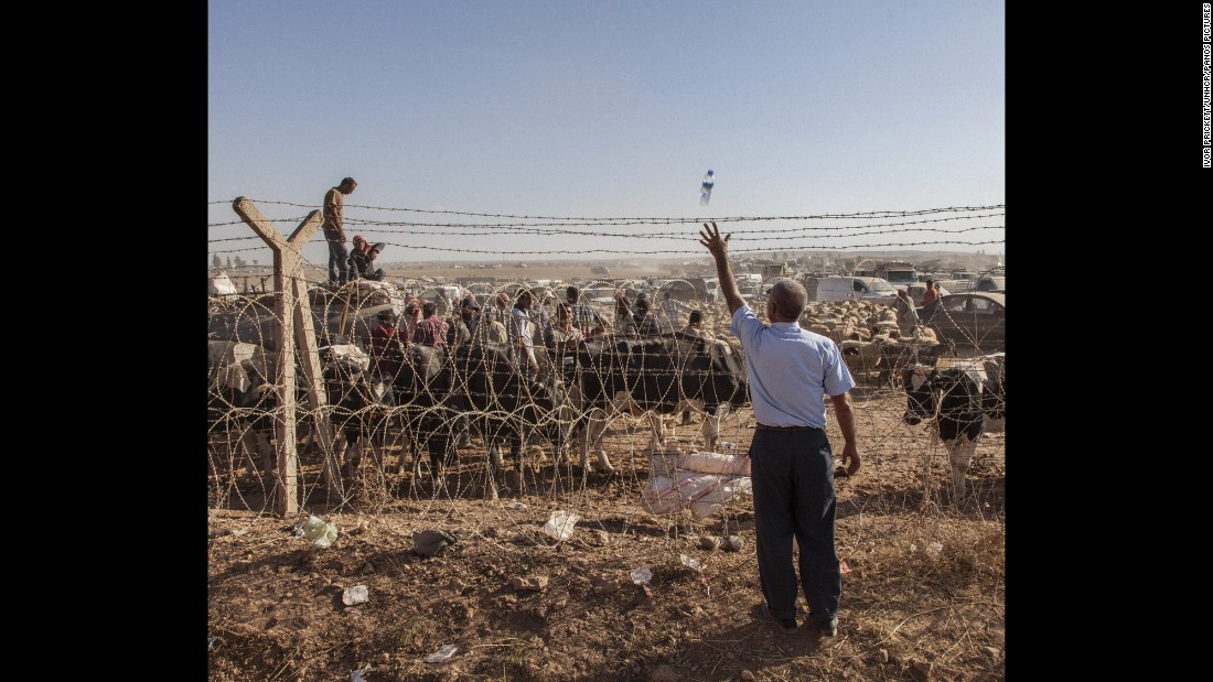 A Turkish man throws a bottle of water across the barbed-wire border fence to a Syrian man waiting on the other side.