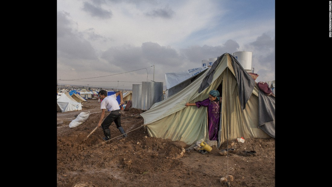 A Syrian refugee digs ditches around his family's tent in the Domiz camp in Iraq.