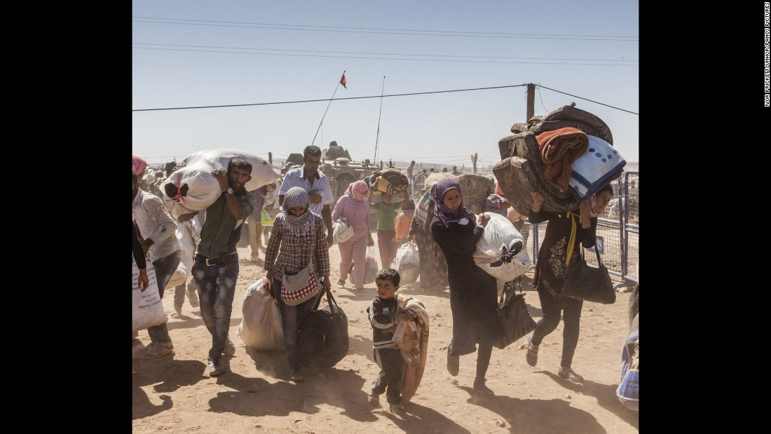 Syrian refugees cross the border into Turkey after fleeing fighting between Kurdish forces and the ISIS militant group.