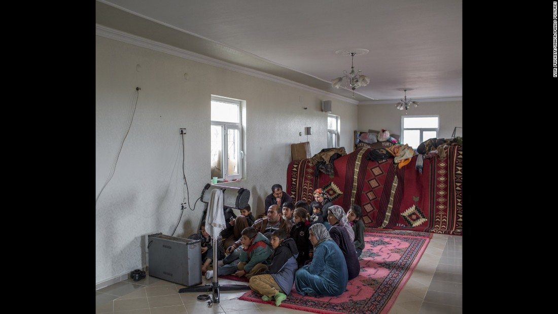 A family of Syrian refugees huddle around the heater while watching television in the unfinished building where they have found refuge in Turkey.