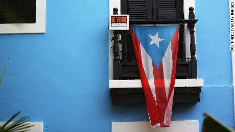 A for sale sign is seen hanging from a balcony next to a Puerto Rican flag in Old San Juan as the island's residents deal with the government's $72 billion debt on July 1, 2015 in San Juan, Puerto Rico.