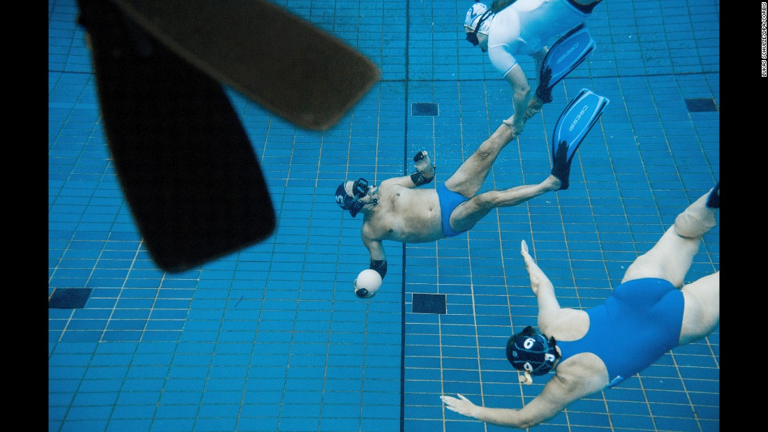 Swimmers play underwater rugby in the public pool at Berlin's Olympic Stadium on Wednesday, July 29. In underwater rugby, players try to place a ball filled with salt water into the basket of the opposing team.