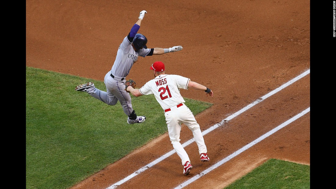 St. Louis' Brandon Moss tags out Colorado's Daniel Descalso during a Major League Baseball game in St. Louis on Saturday, August 1. Descalso played his first five seasons in St. Louis before signing with the Rockies in the offseason.