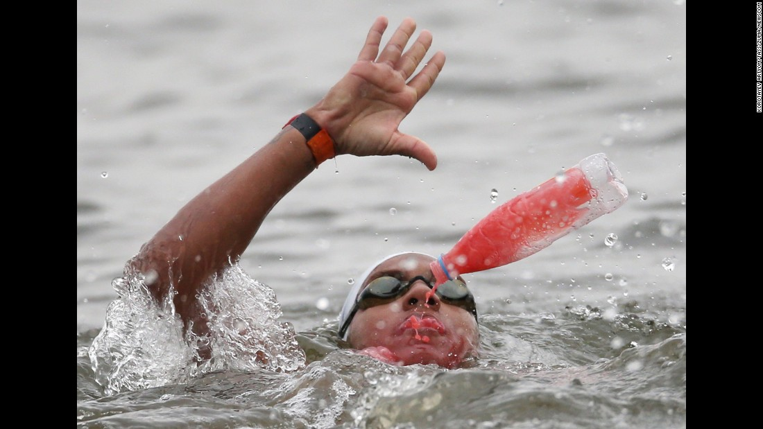 Brazilian swimmer Ana Marcela Cunha takes in what appears to be a sports drink on her way to winning gold in an open-water swimming race Saturday, August 1, at the World Aquatics Championships. She finished the 25-kilometer (15.5-mile) course in five hours, 13 minutes and 47 seconds.