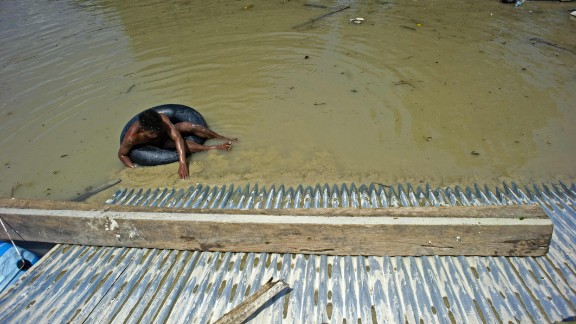 A man climbs to safety on a roof, escaping the flooding in Kalay, Myanmar on August 3.