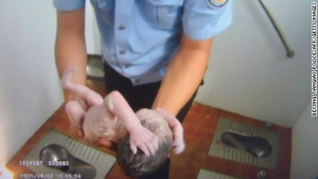 An image supplied by Beijing Tianqiao Police shows an officer holding the baby at the toilet on August 2, 2015.