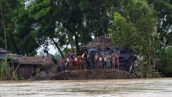 Bangladeshi villagers stand near a broken embankment, avoiding floodwater, in Cox's Bazar on August 2, 2015, after the area was hit by torrential rains from Cyclone Komen.