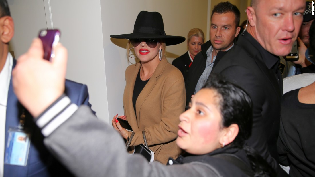 Someone snags a selfie in front of television personality Khloe Kardashian as she arrives at a Sydney airport on Wednesday, July 29.