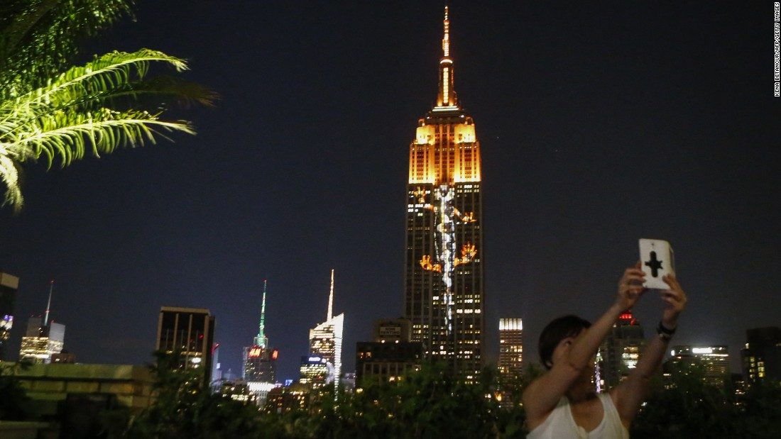 "A woman in New York takes a selfie in front of the Empire State Building on Saturday, August 1. The building's famous light displays <a href=""http://www.cnn.com/2015/08/02/travel/endangered-animals-empire-state-building-lights-feat/"" target=""_blank"">were used to draw attention to endangered wildlife.</a> Along with Cecil the lion, whose death has sparked international outrage, a snow leopard, tigers, lemurs and various snakes, birds and sea creatures were projected onto the building."