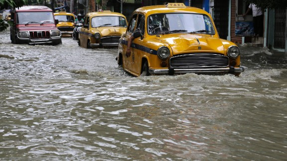 Yellow taxis and other vehicles wade through a flooded street in Kolkata, India, Sunday, Aug. 2, 2015. Parts of the city were flooded after the Ganges river rose following monsoon rains.