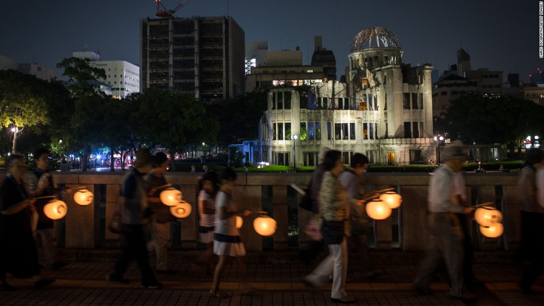 People carry lanterns past the memorial on August 5.
