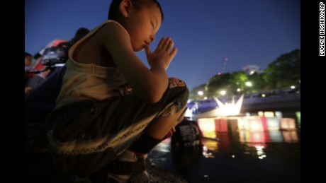 A boy last summer offers prayer after releasing a paper lantern into the Motoyasu River, where thousands of atomic bomb victims died in 1945.