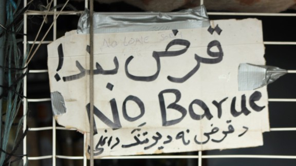 """A sign reads """"no credit"""" in three languages. Shopkeepers don't give loans to customers who they know might be on a truck across the English Channel the next day."""