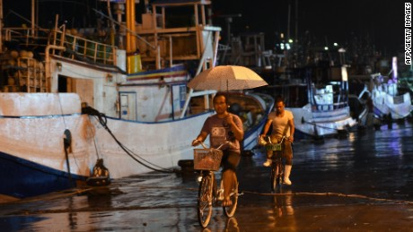 Workers ride past fishing boats moored in a shelter at Nanfangao harbour in Yilan on August 6, 2015 as typhoon Soudelor approaches eastern Taiwan. The strongest typhoon of the year was bearing down on Taiwan's east coast on August 6, forcing the evacuation of more than 2,000 from outlying islands popular with tourists. AFP PHOTO / Sam YehSAM YEH/AFP/Getty Images
