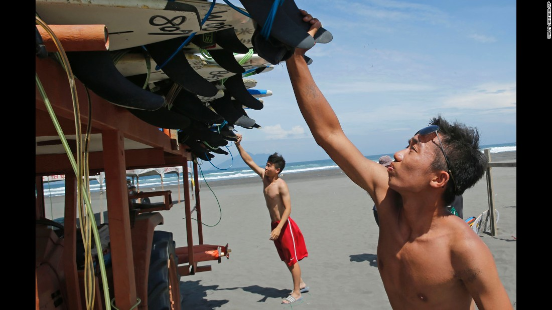 Surfers remove surf boards from a beach in Yilan County, Taiwan, Thursday, August 6.