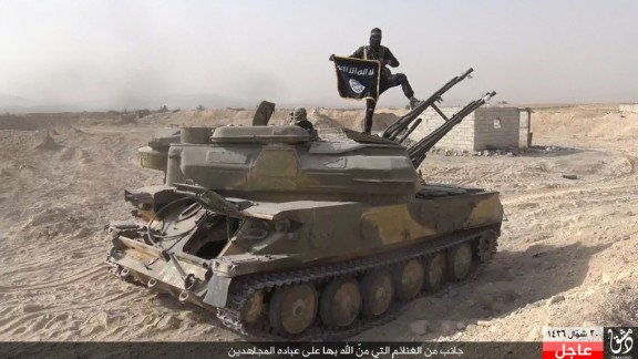 In this image taken from social media, an ISIS fighter holds the group's flag after the militant group overran the Syrian town of al-Qaryatayn on Thursday, August 6, the London-based Syrian Observatory for Human Rights reported. ISIS uses modern tools such as social media to promote reactionary politics and religious fundamentalism. Fighters are destroying holy sites and valuable antiquities even as their leaders propagate a return to the early days of Islam.