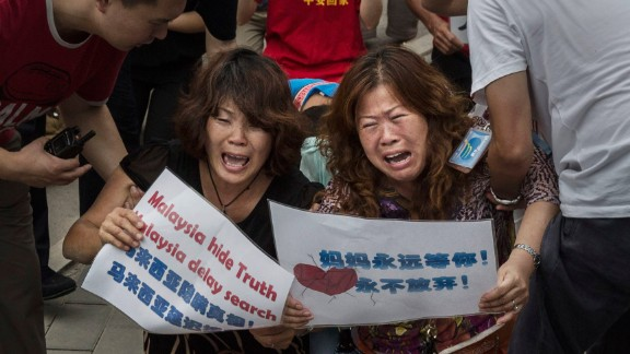 BEIJING, CHINA - AUGUST 07: Chinese relatives of passengers missing on Malaysian Airlines flight MH370 cry as they kneel in front of the media outside the Malaysian Embassy during a protest by relatives on August 7, 2015 in Beijing, China. France expanded its search for debris off Reunion Island Friday a day after Malaysia