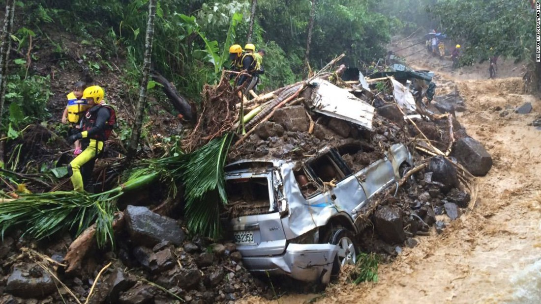 Emergency rescue personnel carry children past cars crushed by a mudslide in New Taipei City on August 8.