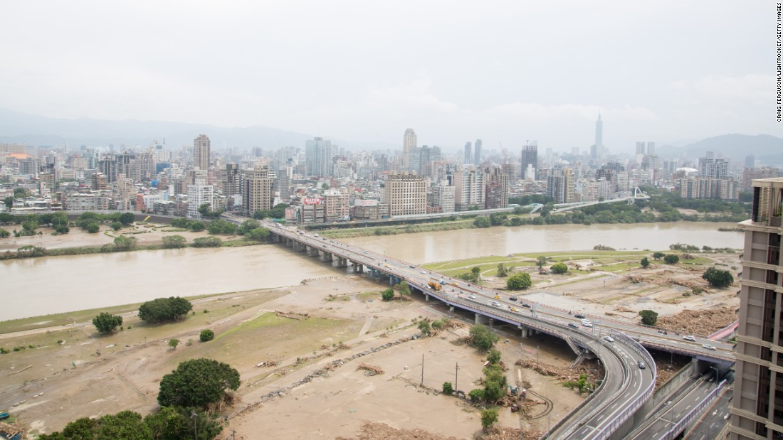 Piles of debris left by Typhoon Soudelor's heavy rain and flooding lie under the Zhongzheng Bridge as it crosses the Xindian River in Taipei.