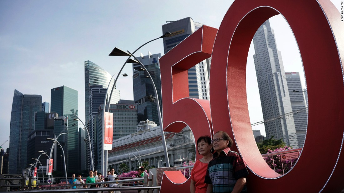 A couple pose in front of a giant number 50 commemorating Singapore's 50th year of independence.