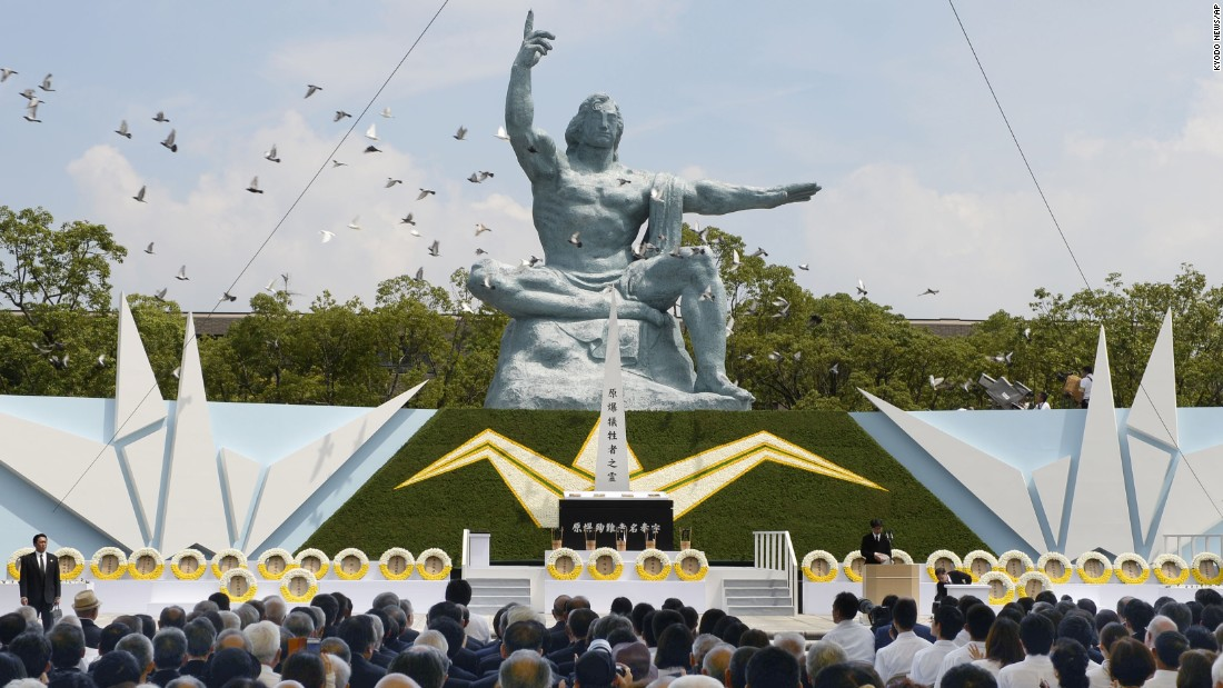 Doves fly over the Statue of Peace at Nagasaki Peace Park.