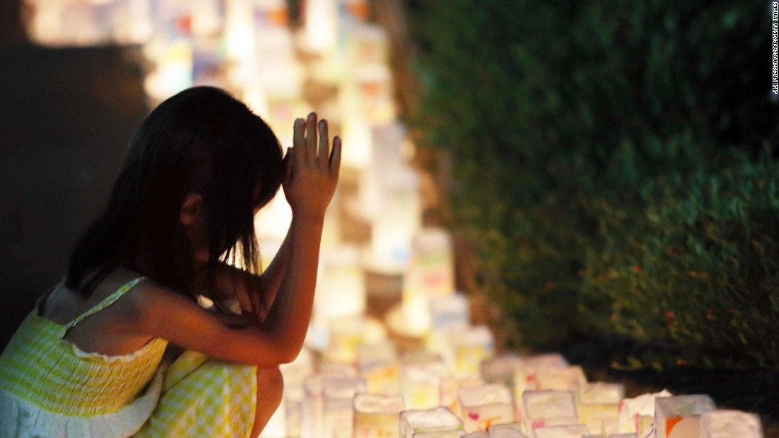 A girl offers a prayer to the victims before lanterns are placed at the Peace Memorial Park in Nagasaki on Saturday, August 8.