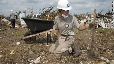 AmeriCorps volunteer Teri Jacobs picks up tornado debris in June 2011 in Joplin, Missouri.