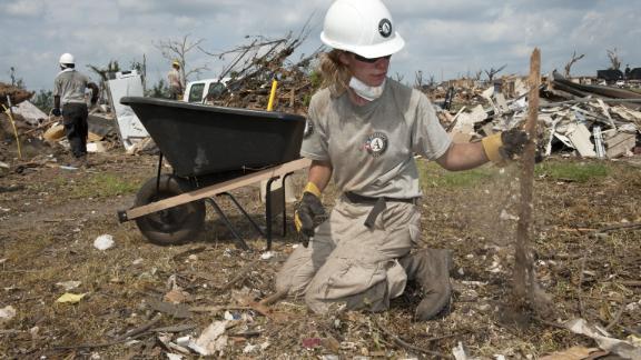 AmeriCorps volunteer Teri Jacobs picks up tornado debris in June 2011 in Joplin, Missouri.