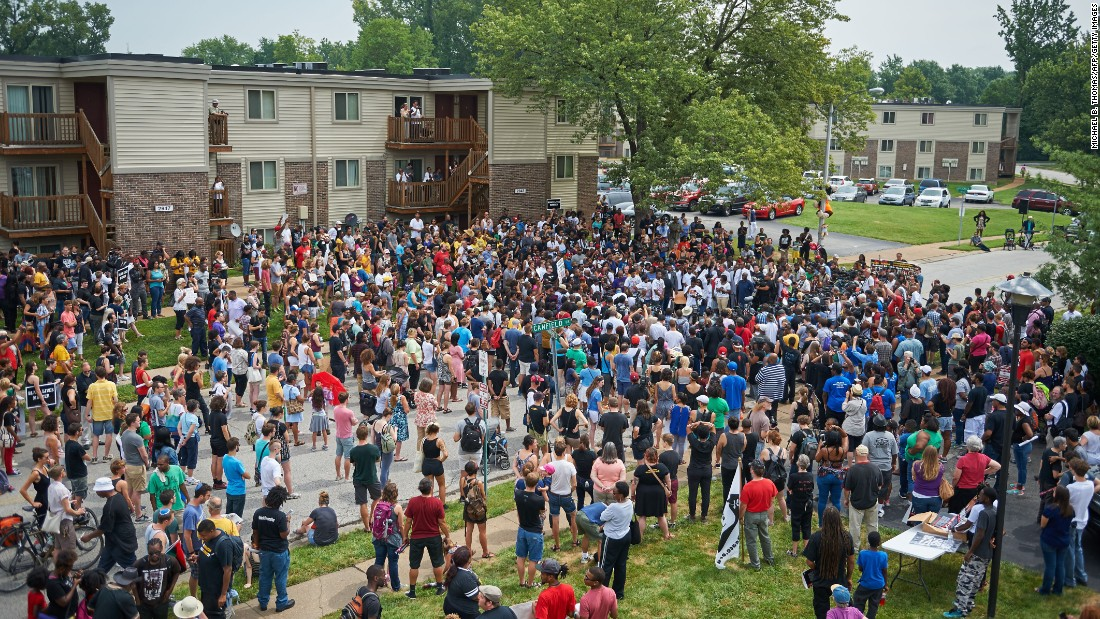 People attend a memorial service outside Canfield Apartments in Ferguson on August 9. Several hundred demonstrators stood in silence at the spot where Brown was shot and killed.
