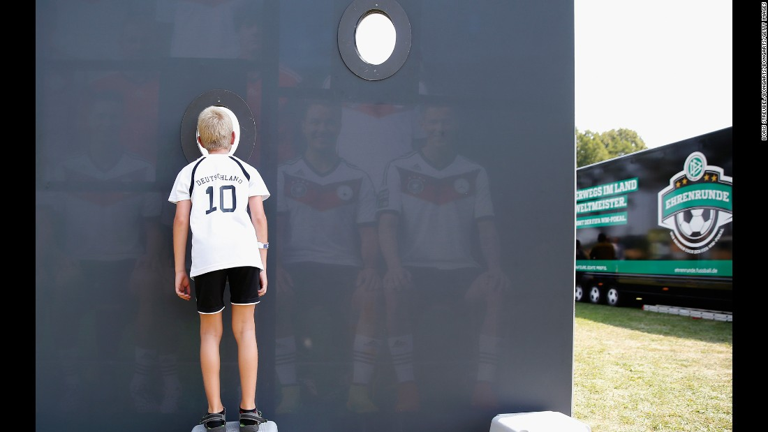 A young fan looks through a cutout in a team photo at the DFB Ehrenrunde on Friday, August 7, in Torgau, Germany.