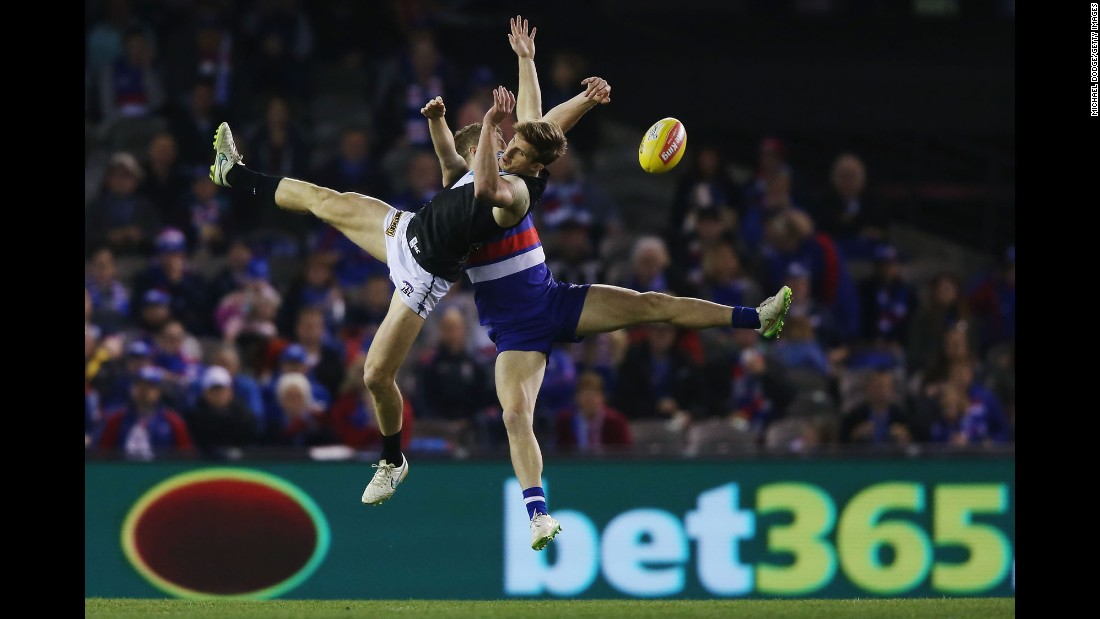 Hamish Hartlett of the Power, left, and Lachie Hunter of the Bulldogs compete for the ball during the round 19 AFL match between the Western Bulldogs and Port Adelaide Power on Saturday, August 8, in Melbourne.