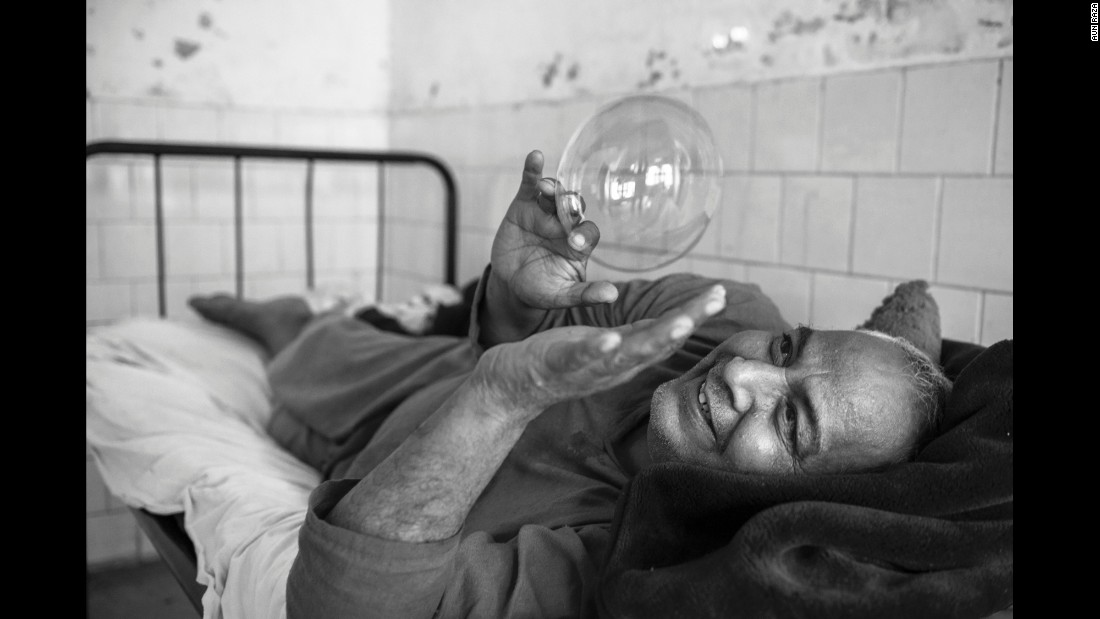 A patient plays with a soap bubble inside a mental hospital in Lahore, Pakistan. Photographer Aun Raza documented the lives of patients there from 2011 to 2014.