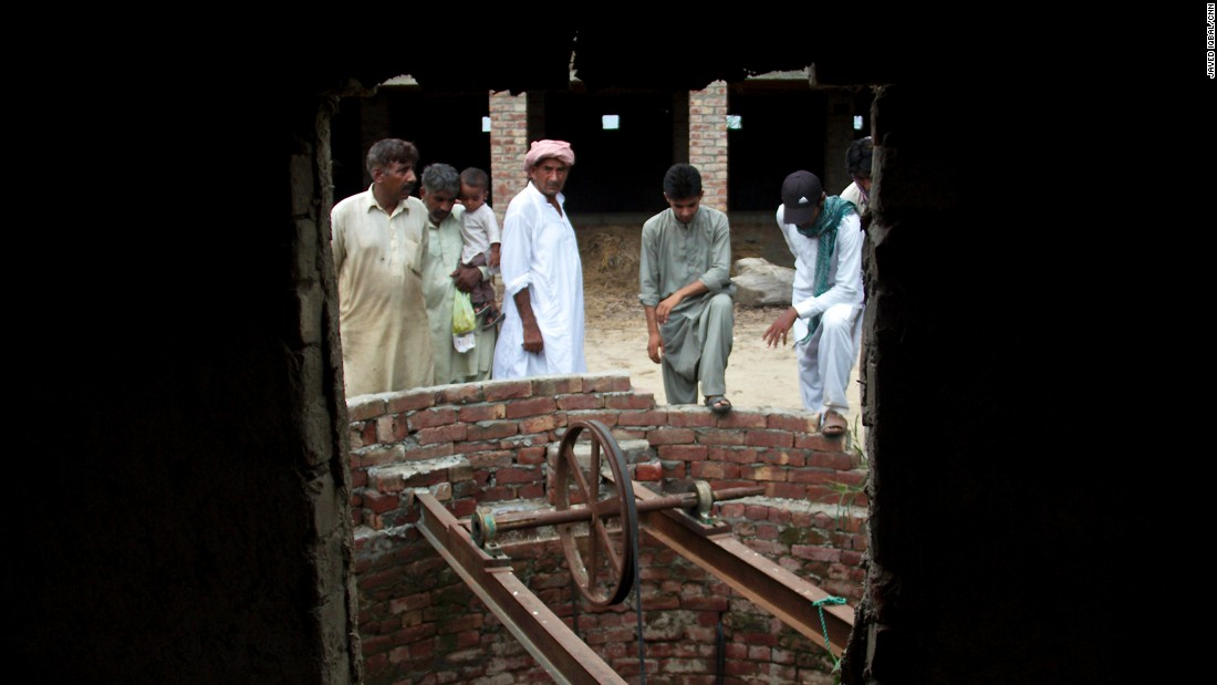 Villagers peer into a well in the house where some children were allegedly drugged, raped and filmed. Locals told CNN this well was where children were hung naked upside down.