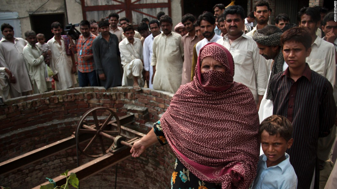 The mother of one of the suspects protests her family's innocence as angry villagers look on.