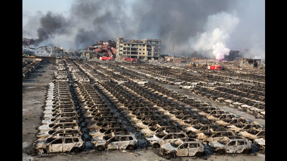Smoke from the explosion billows over destroyed cars. As of 2014, Tianjin was the world's 10th-busiest container port, according to the World Shipping Council.