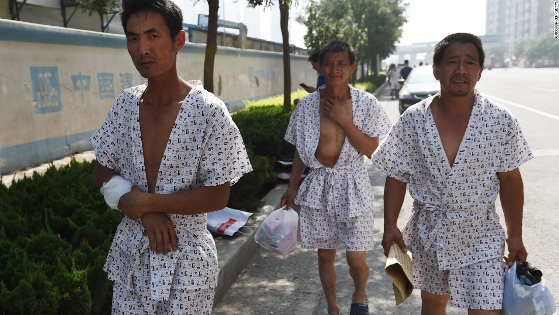 Three men walk out onto the streets after being treated at a hospital on Thursday, August 13.