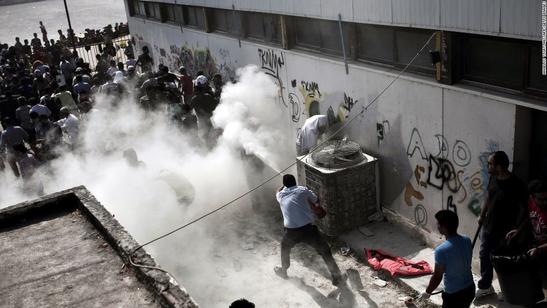 Policemen try to disperse hundreds of migrants by spraying them with fire extinguishers during a gathering for a registration procedure at a stadium on the Greek island of Kos, on Tuesday, August 11.  The migrants had been ordered to go to the stadium by police who carried out a sweep of parks and public squares where they'd congregated. With no shade, toilets or water provided, the situation deteriorated.