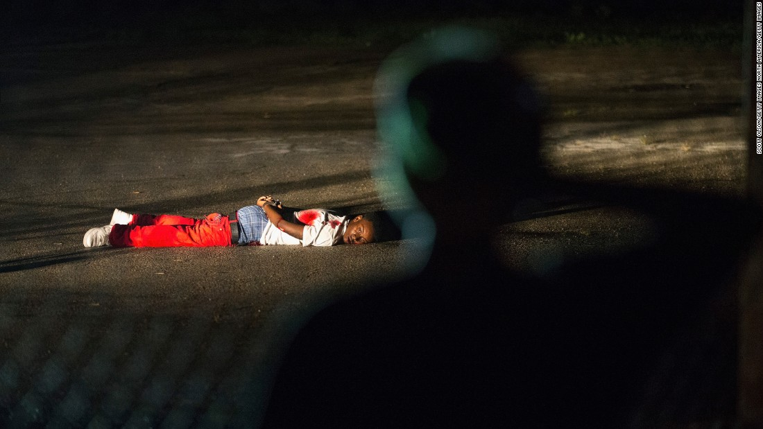 "The <a href=""http://www.cnn.com/2015/08/10/us/gallery/ferguson-protests-anniversary/index.html"">anniversary observations</a> of unarmed teenager Michael Brown's shooting death by a white Ferguson, Missouri, police officer were shattered that same night when gunfire broke out, sending protesters and police scattering to safety. The accused gunman, 18-year-old Tyrone Harris of St. Louis, lies arrested on the ground before being hospitalized in critical condition. The St. Louis County Police Department said officers shot the teenager after he unleashed a ""remarkable amount of gunfire"" at police, a characterization the man's aunt contends is not true."