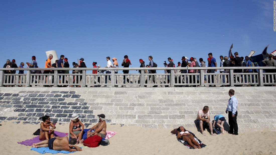 Migrants protest near sunbathers on the beach in Calais, France, on Saturday, August 8.