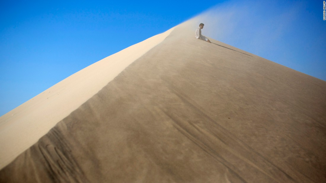 Luis Enrique Tuanama, 17, rests while climbing the Cerro de Saraja  a mountain of sand in Ica, Peru, on Friday, August 7.