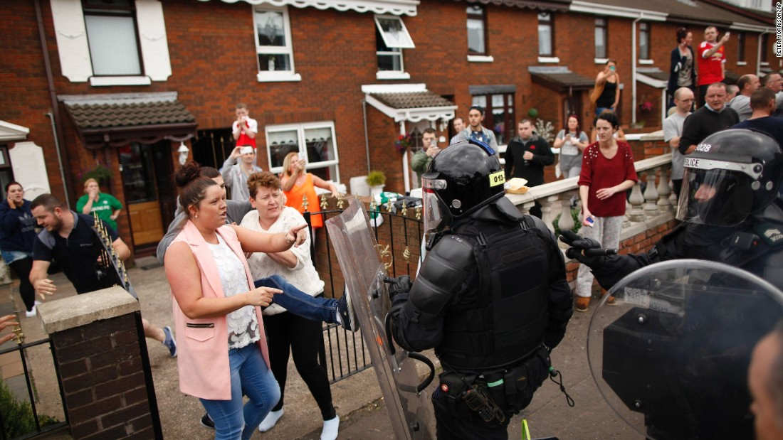 Riot police clear the streets in the Oldpark area of Belfast, Northern Ireland, on Sunday, August 9, after a controversial anti-internment rally was stopped by police.