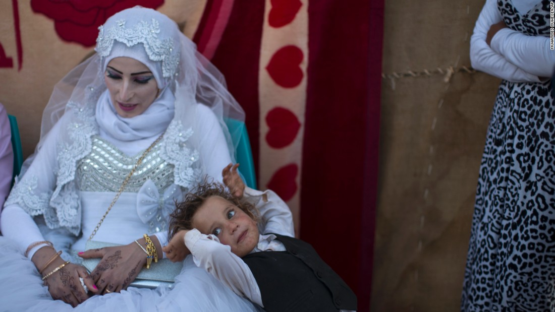 A Syrian refugee leans against bride Fatheya Mohammed, 21, during her wedding ceremony at an informal tented settlement on the outskirts of Mafraq, Jordan, near the Syrian border, on Friday, August 7.