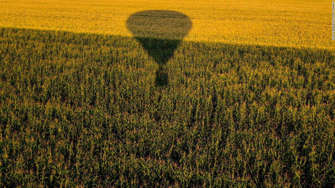 A hot air balloon flies over a field near Budapest during the 19th FAI Hot Air Balloon European Championship on Wednesday, August 12.