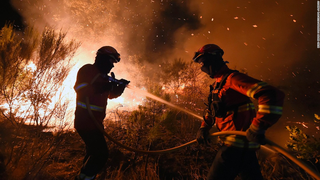 Firefighters try to extinguish a wildfire in Mangualde, Portugal, on August 11.