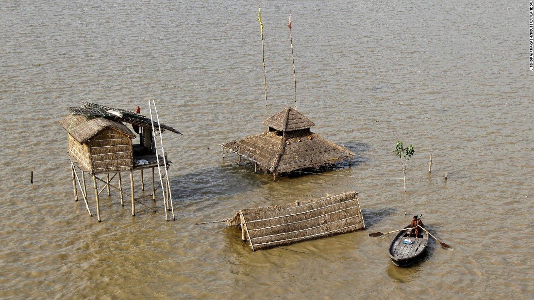 A Sadhu, or Hindu holy man, rows a boat near submerged huts on the flooded banks of the Ganges River on Tuesday, August 11. Torrential monsoon rains in the aftermath of Cyclone Komen continue to cause flooding in India, Bangladesh and other South Asian countries, leaving hundreds dead and millions displaced.