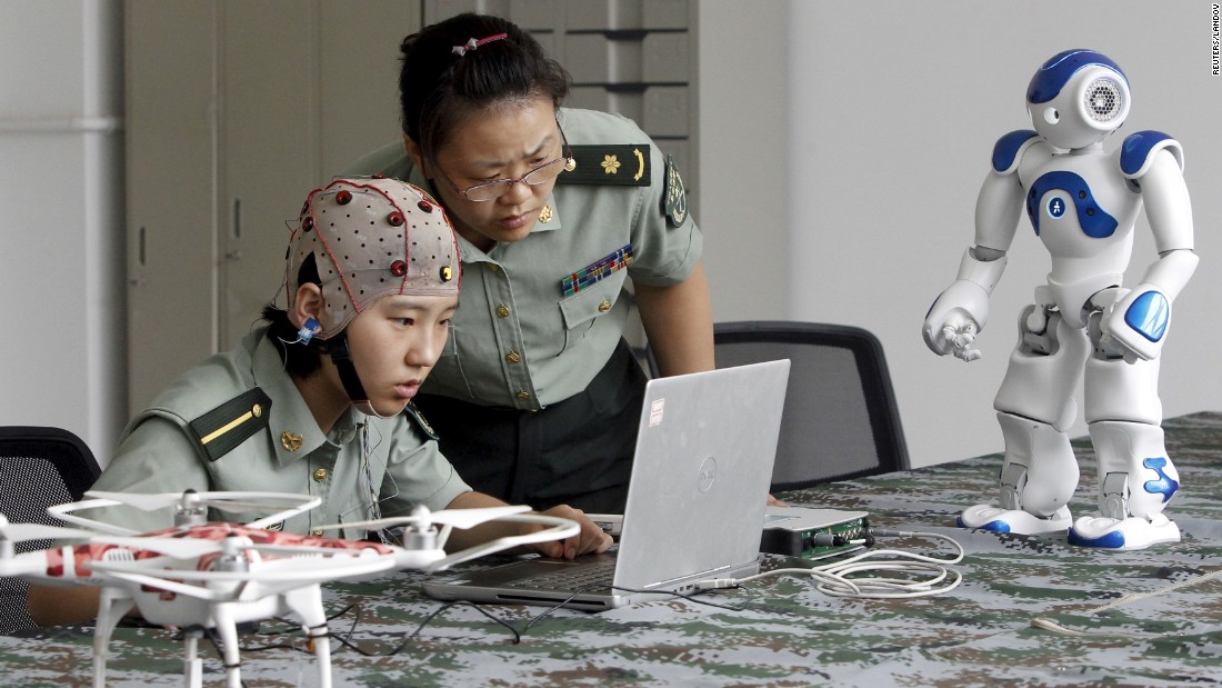 A student and instructor look at a computer as they use a headset to control a robot with her mind at the People's Liberation Army Information Engineering University in Zhengzhou, China, on Friday, August 7. The robots can be controlled through the headset to go different directions, turn their heads and pick up objects, local media reported.