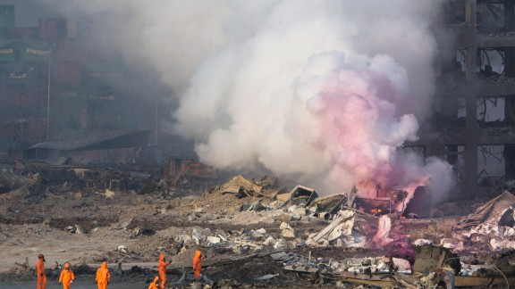 "Firefighters wear protective gear while working as partially pink smoke billows nearby. The environmental group Greenpeace expressed concern ""that certain chemicals will continue to pose a risk to the residents of Tianjin,"" and city residents shared similar fears on social media."