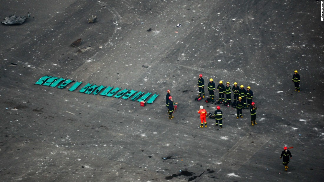 Rescuers are seen near the site of the blasts. A Chinese military team of nuclear and chemical were conducting investigations as pressure grew on authorities to explain the cause of the fire and the resulting cataclysmic explosions.